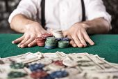 image of gangster  - Close-up hand of young gangster man while playing poker game with money chips and cards. ** Note: Shallow depth of field - JPG