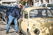 pic of beetle car  - Man with an old classic yellow street wolsvagen beetle - JPG