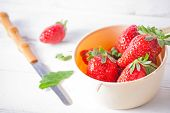 Fresh strawberries in strainer close up and a knife