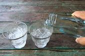 Fresh water in glass on wooden table.