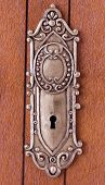 stock photo of keyhole  - close up photo of keyhole with ornament on wooden door - JPG