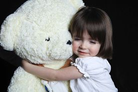 stock photo of girlie  - a little girl with bear on a black background - JPG