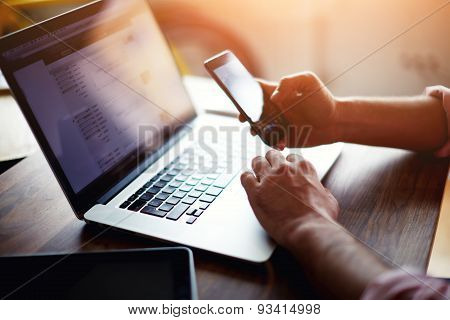 Side view of a man\'s hands using smart phone in interior  at his coworking place using technology