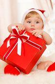 stock photo of santa baby  - Baby santa holds a big red gift box - JPG