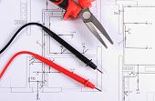 stock photo of pliers  - Cables of multimeter and metal pliers lying on construction drawings of house electrical drawings and work tools for engineer jobs - JPG