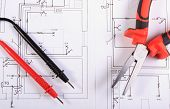 pic of electrical engineering  - Cables of multimeter and metal pliers lying on electrical construction drawings of house electrical drawings and tools for engineer jobs - JPG