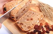 image of fresh slice bread  - Slicing fresh baked wholemeal bread ears of wheat and heap of raisins lying on cutting board concept for healthy eating - JPG