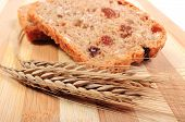 stock photo of fresh slice bread  - Slice of fresh baked wholemeal bread and ears of wheat lying on cutting board concept for healthy eating - JPG