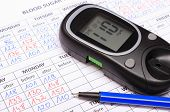 picture of measurements  - Glucose meter and blue pen lying on medical forms for measurement sugar in blood results of measurement of sugar concept for measuring sugar level - JPG