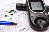 foto of measurements  - Glucose meter lancet device and pen lying on medical forms for measurement sugar in blood results of measurement of sugar concept for measuring sugar level - JPG