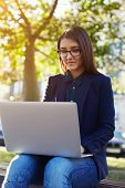 image of work bench  - Portrait of young student girl in glasses sitting on the campus bench while use laptop gadget during her class break attractive and elegant woman working on laptop sitting outdoors at sunny day - JPG