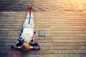 pic of jetties  - Top view young woman lying on a wooden jetty enjoying the sunshinetourist girl in bright summer glasses lying on jetty by river vintage photo of relaxing young woman in nature with tablet flare sun