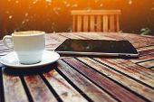 stock photo of coffee coffee plant  - Shot of a digital tablet smart phone and and coffee mug on a wooden table with empty chair black touch screen computer on cafe table with coffee cup flare sun light - JPG