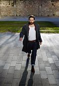 Постер, плакат: Portrait of attractive strong man is dressed stylish walking the streets on a sunny day