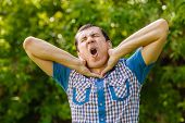 stock photo of choke  - Man on the street choking himself hands on a green background leaves  summer - JPG