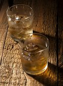 stock photo of scotch  - Glasses of scotch on wooden vintage background with copyspace - JPG