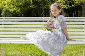 stock photo of polite girl  - Child with flowers rests on a bench - JPG