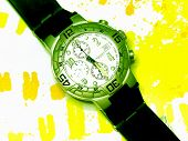 picture of wrist  - High Angle View of Stylish Wrist Watch with Green Metal Face and Various Functions and Black Strap Against Wild Patterned Yellow Paint Splatter Background - JPG