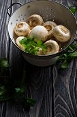 stock photo of champignons  - Fresh white champignons in a colander on dark wooden table - JPG