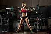 foto of execution  - beautiful girl bodybuilder execute exercise with weight in dark gym - JPG