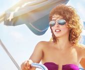 stock photo of swimsuit model  - Portrait of a woman driving sailboat - JPG