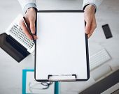 picture of medical equipment  - Doctor writing medical records on a blank sheet and holding a clipboard medical equipment and desktop on background top view - JPG