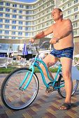 foto of bathing  - Elderly man in bathing suits on bikes on the hotel in the evening - JPG