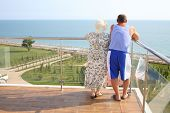 picture of vest  - Elderly man in striped vest with wife standing on the balcony - JPG