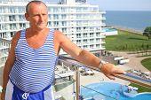 stock photo of vest  - Portrait of elderly man in striped vest on the terrace - JPG