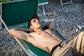 stock photo of sunbather  - Shirtless Young Man Drying Off in Hot Sun - JPG
