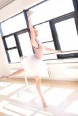 image of ballet barre  - Young Smiling Ballerina Wearing Pink Tutu Doing Barre Exercises in Sunny Dance Studio - JPG