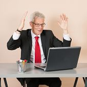 stock photo of chokers  - Senior man happy while working with laptop at the office - JPG