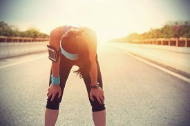 pic of fatigue  - tired woman runner taking a rest after running hard on city road - JPG