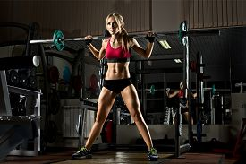 picture of slender  - beautiful girl bodybuilder execute exercise with weight in dark gym - JPG