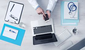 stock photo of touching  - Doctor working at office desk and using a mobile touch screen phone computer and medical equipment all around top view - JPG