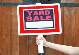 picture of yard sale  - Wooden Yard Sale sign in female hand on wooden fence background - JPG