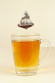 stock photo of brew  - Tea bags over the glass with freshly brewed tea - JPG
