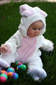 stock photo of easter eggs bunny  - Baby Boy in an easter bunny outfit collects easter eggs - JPG