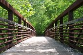 stock photo of arch foot  - An arched iron and wooden foot bridge in a greenway park as seen from one end to the other - JPG