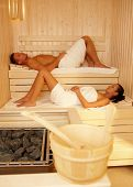 Relaxing in sauna, young couple enjoying healthy wellness.?