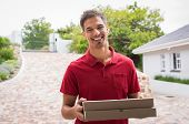 Smiling young delivery man holding pizza boxes outdoor. Happy deliveryman in red t-shirt holding two poster