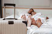 Blurry image of beautiful couple man and woman in white bathrobe lying and resting together on bed i poster