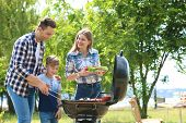 Happy Family Having Barbecue With Modern Grill Outdoors poster