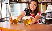 Young Cheerful Happy Bartender Girl Looking At Camera And Offering Beer To Customers. Happy Smiling  poster