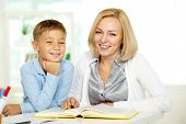 stock photo of diligent  - Portrait of pretty tutor and diligent pupil looking at camera with smiles - JPG