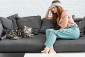 Attractive Young Woman Sitting On Couch With Tabby Cat poster