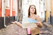 Woman Lost In The City. Confused Traveler Holding Map And Spreading Hands In Old Town. Disappointed  poster