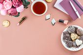 Flat Lay Home Office Desk. Feminine Workspace With Note Pad, Pink Flowers Bouquet, Tea, Chocolate Co poster