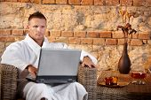 Wellness with laptop computer, young man in bathrobe looking at screen, sitting in armchair.?