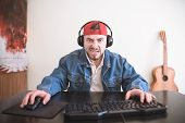 Angry Man Is Sitting At The Table And Playing Video Games. Portrait Of Amazed Gamers Man Playing Th poster
